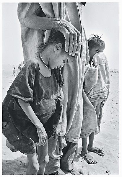 Während der Dürre, die zur Hungersnot in der Sahelzone führte. Die Gesichter zum Schutz gegen Hitze und Wind verhüllt, marschieren Frauen und Kinder durch die Wüste. Mali, 1985.