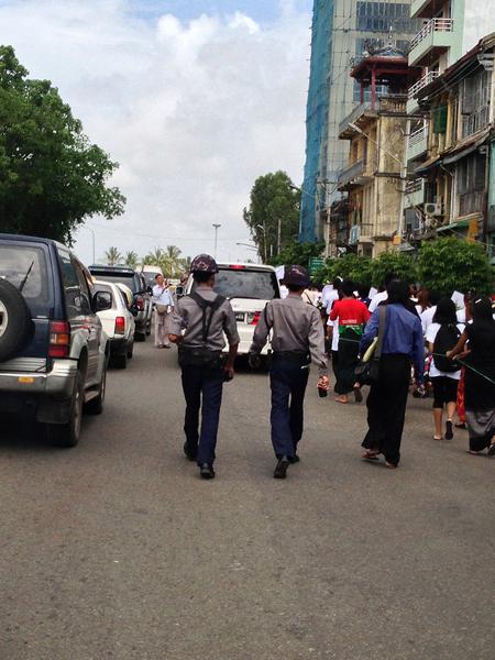 Zwei Polizisten überwachen einen Demonstrationszug in Rangun. Oft mischen sich auch Agenten in zivil unter die Menge, um Informationen über die Teilnehmer einer solchen Demonstration zu sammeln.