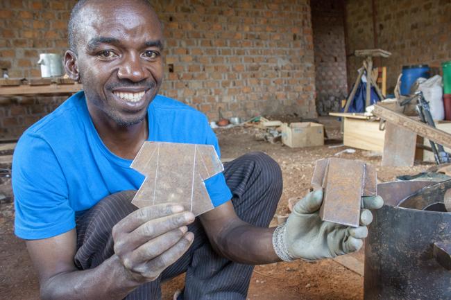 Adelard Ndibalema, Kochherd-Techniker bei der Organisation CHEMA in Kayanga, mit Bauteilen eines Mikrovergasers