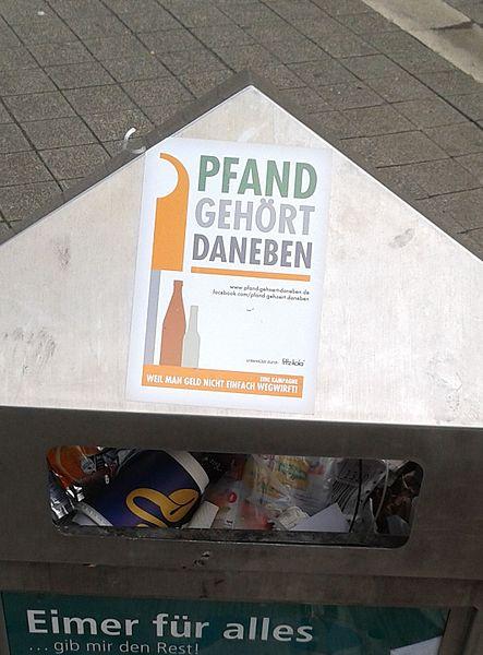 Mülleimer in Bielefeld mit Werbeaufkleber für die Aktion Pfand gehört daneben